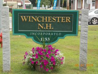 """Short wooden sign """"Winchester NH"""" suspended between 2 granite poles, with flowers below"""